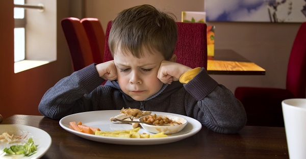 This kid is not excited about his beans. Don't be like this kid. Image via iStock.